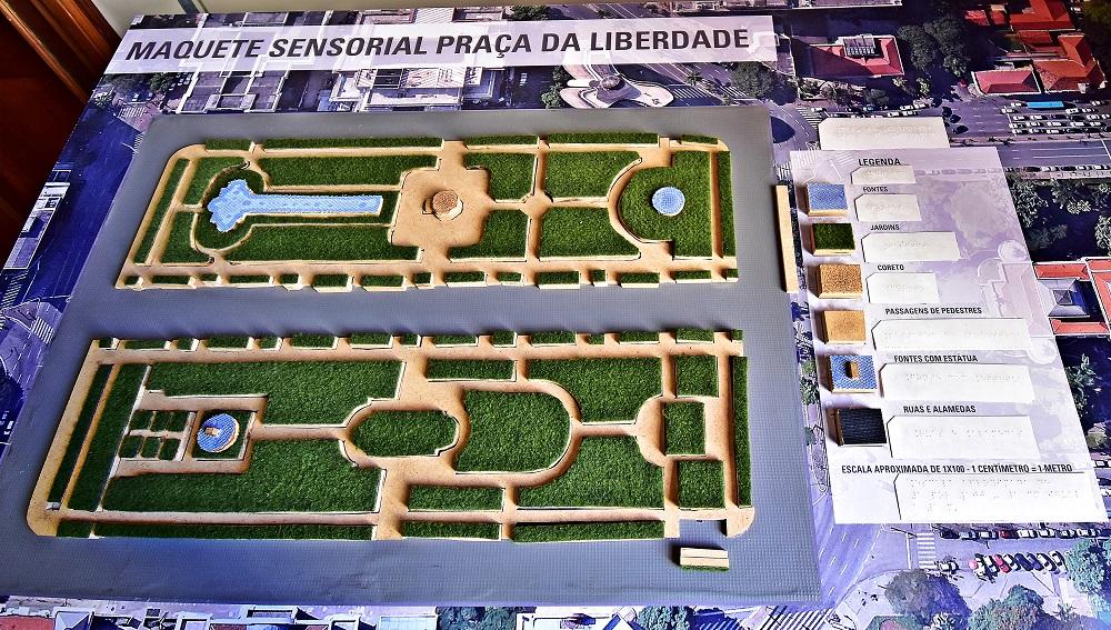 Maquete sensorial da Praça da Liberdade vista de cima, mostrando a maquete e a legenda em Braille.