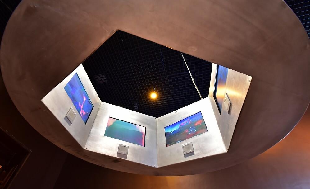 Vista debaixo da roda imersiva, que consiste em um círculo com uma sequência de televisores e equipamentos de áudio, que mostram imagens e locuções sobre o Alumínio.