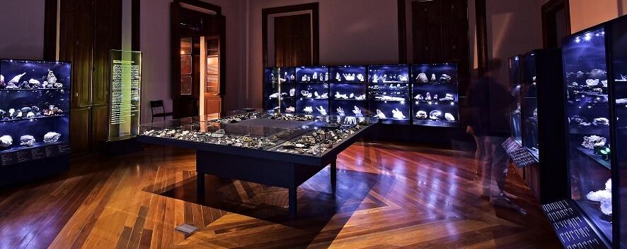 Galeria do museu com diversos expositores em vidro contendo muitas amostras de minerais e gemas.