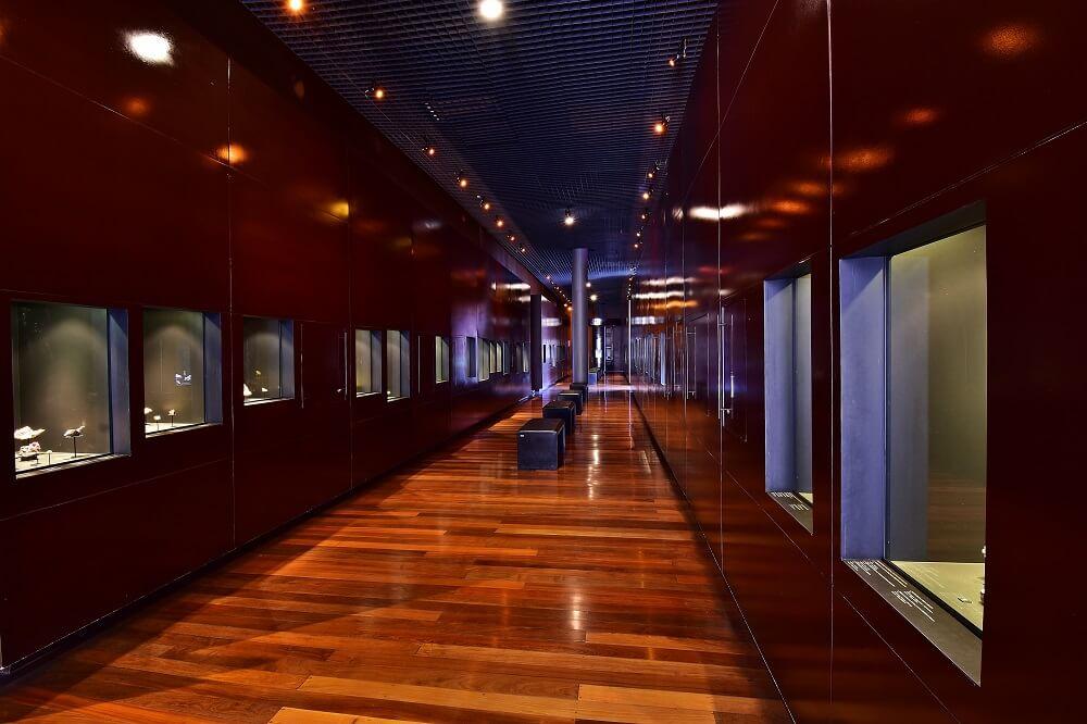 Galeria do Inventário Mineral, com bancos para os visitantes se sentarem e sequência de janelas com minerais, gemas e meteoritos em exposição.