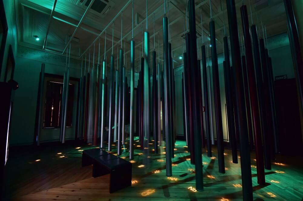 Banco onde os visitantes podem ouvir o áudio sobre Mendeleev e escultura de tubos e projeções, homenageando os elementos químicos da tabela periódica.