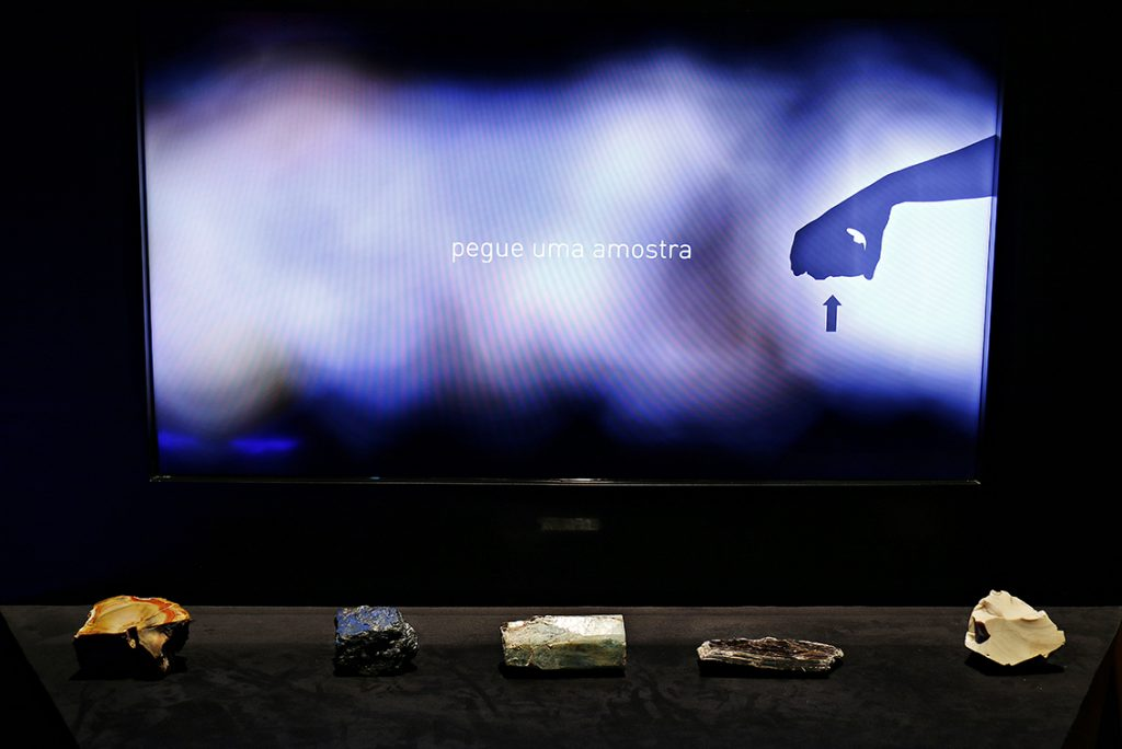 """Expositor Pedras Sabidas com cinco amostras, pronto para ser utilizado. No televisor aparece a mensagem: """"Pegue uma amostra""""."""