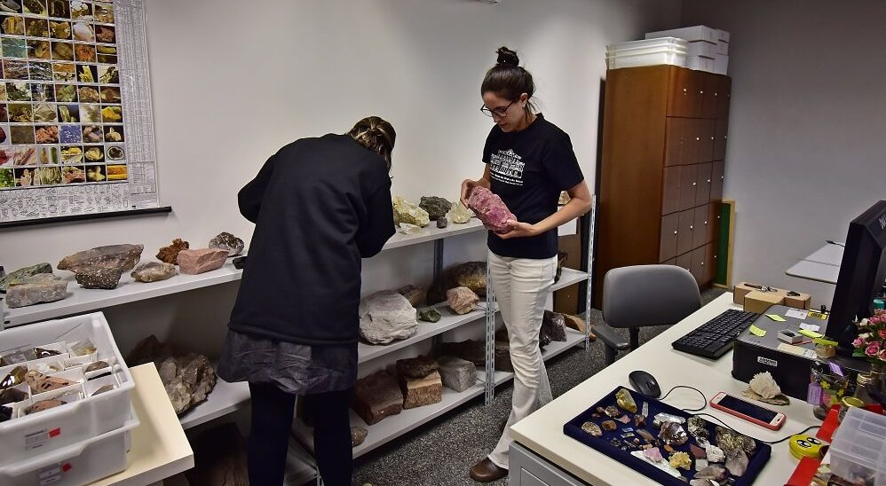 Andréa e Tamires, funcionárias do museu, escolhendo as amostras de minerais na reserva técnica.
