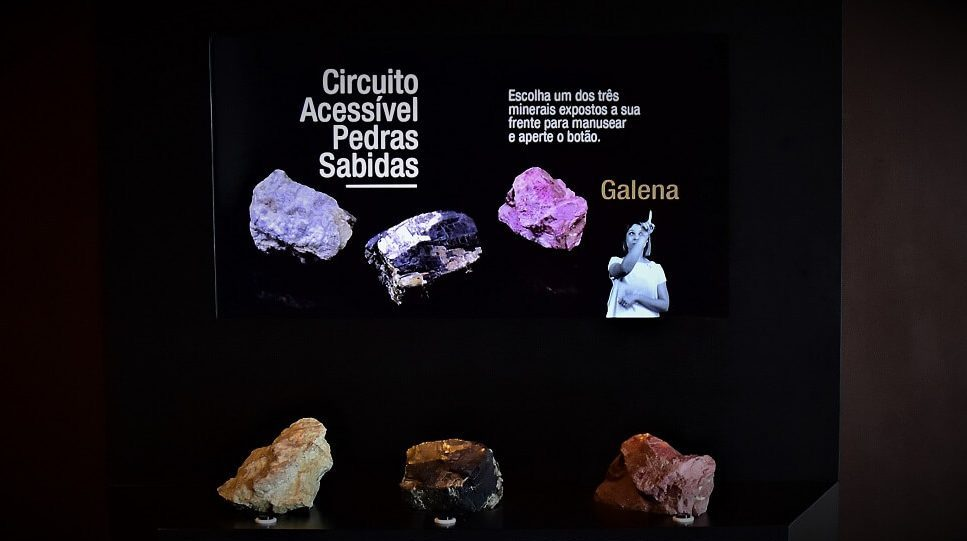 """Interface interativa com três amostras de minerais e tela, onde se lê: """"Circuito Acessível Pedras Sabidas""""."""