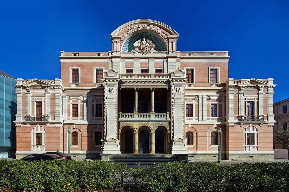 """Fachada principal do Museu das Minas e do Metal, com duas grandes colunas, várias janelas, três andares e um brasão no alto onde se lê: """"Secretaria da Educação""""."""