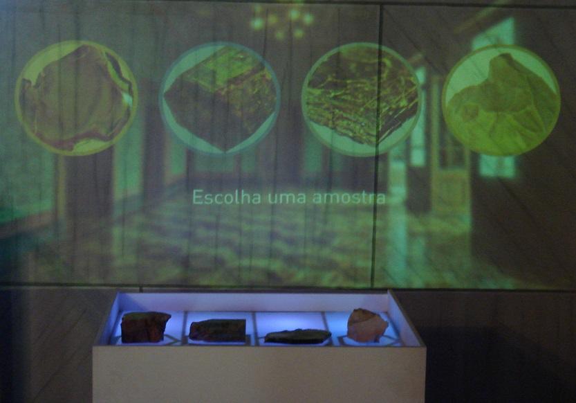 """Mobiliário do protótipo das Pedras Sabidas, branco com luzes roxas, contendo quatro amostras de minerais. Projeção de imagens na parede do museu contendo o texto: """"Escolha uma amostra""""."""