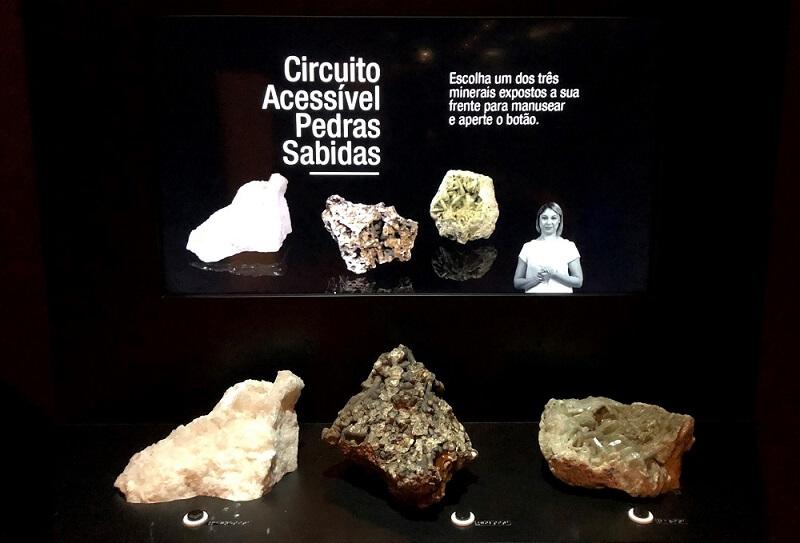"""Três amostras de minerais estão no expositor, à frente de uma tela que diz: """"Circuito Acessível Pedras Sabidas: Escolha um dos três minerais expostos a sua frente para manusear e aperte o botão."""""""